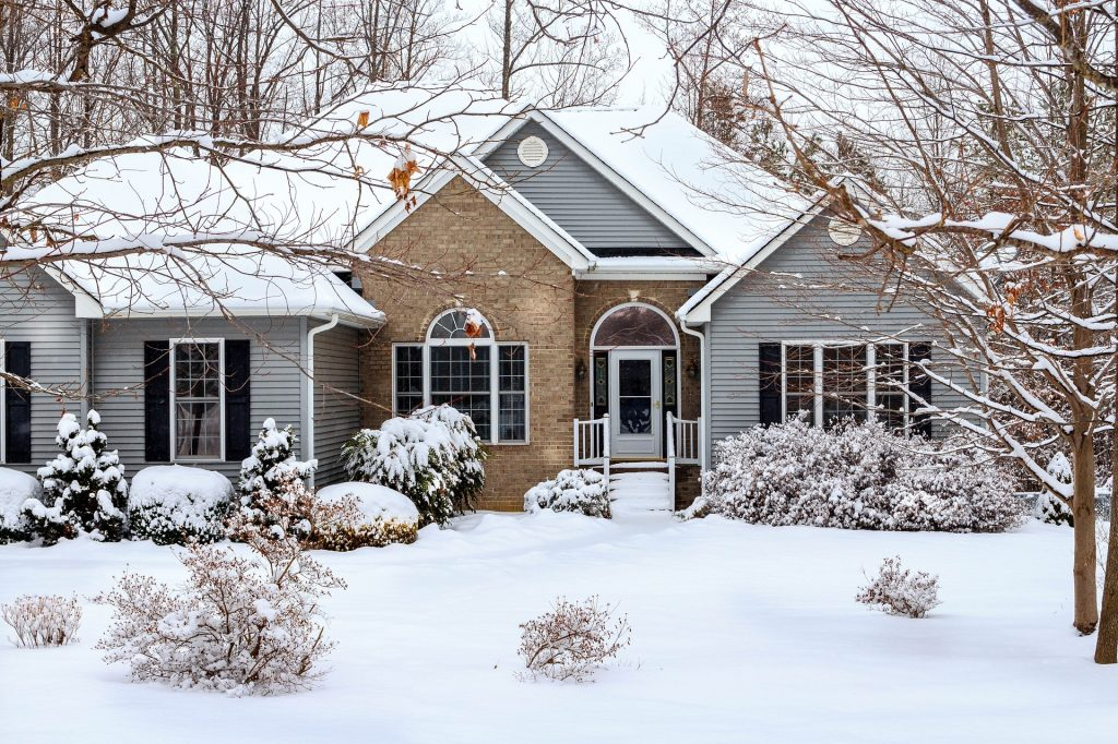 winter, house covered with snow, vinyl siding, brick accent wall